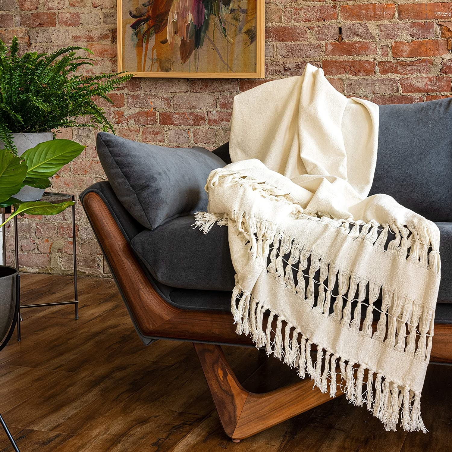 Tasseled throw blanket with woven fabric in throughout edges and center