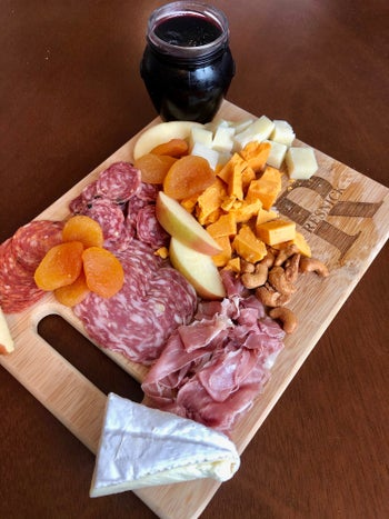 a custom carving board with a cheese and meat spread on it