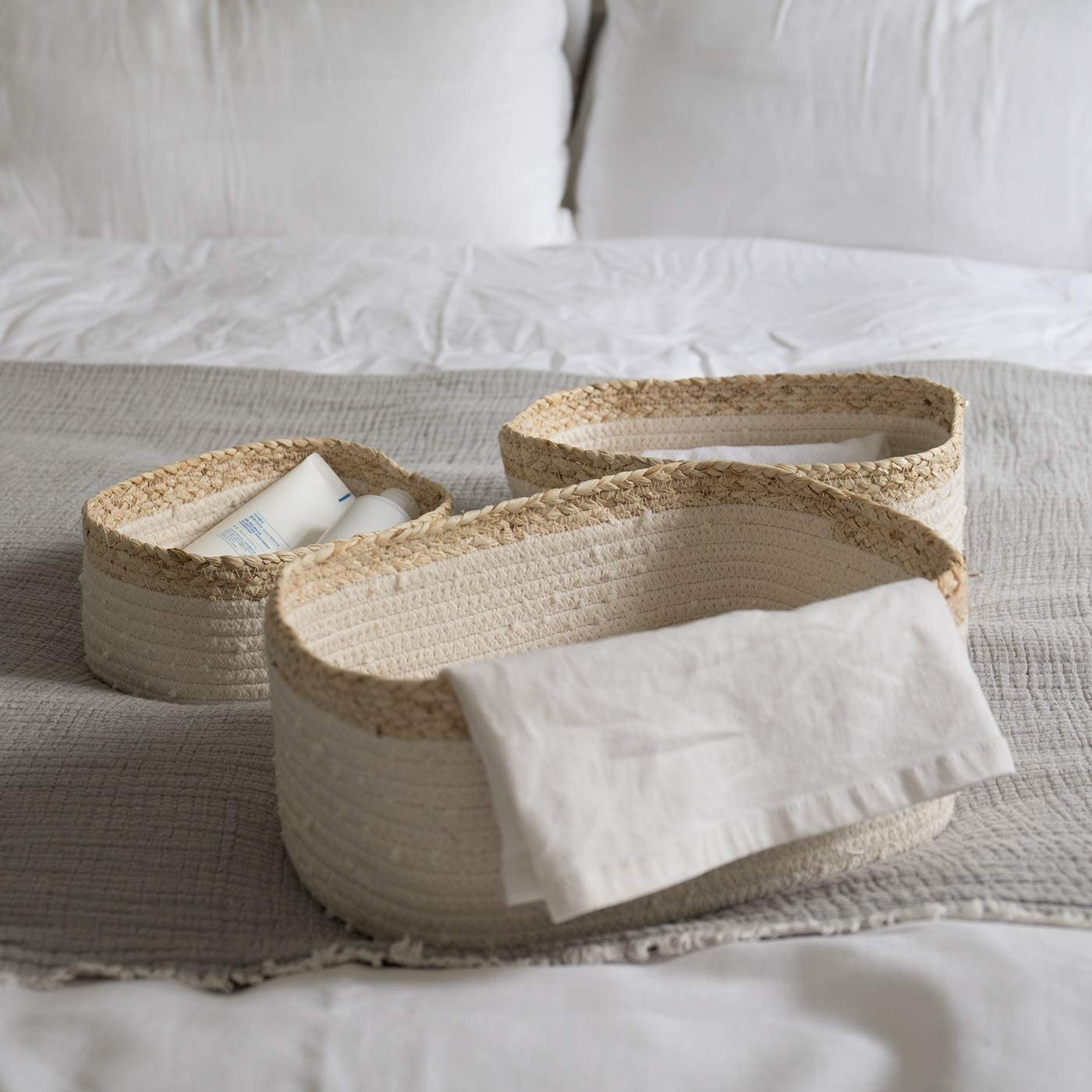 Three woven storage baskets in natural color and white