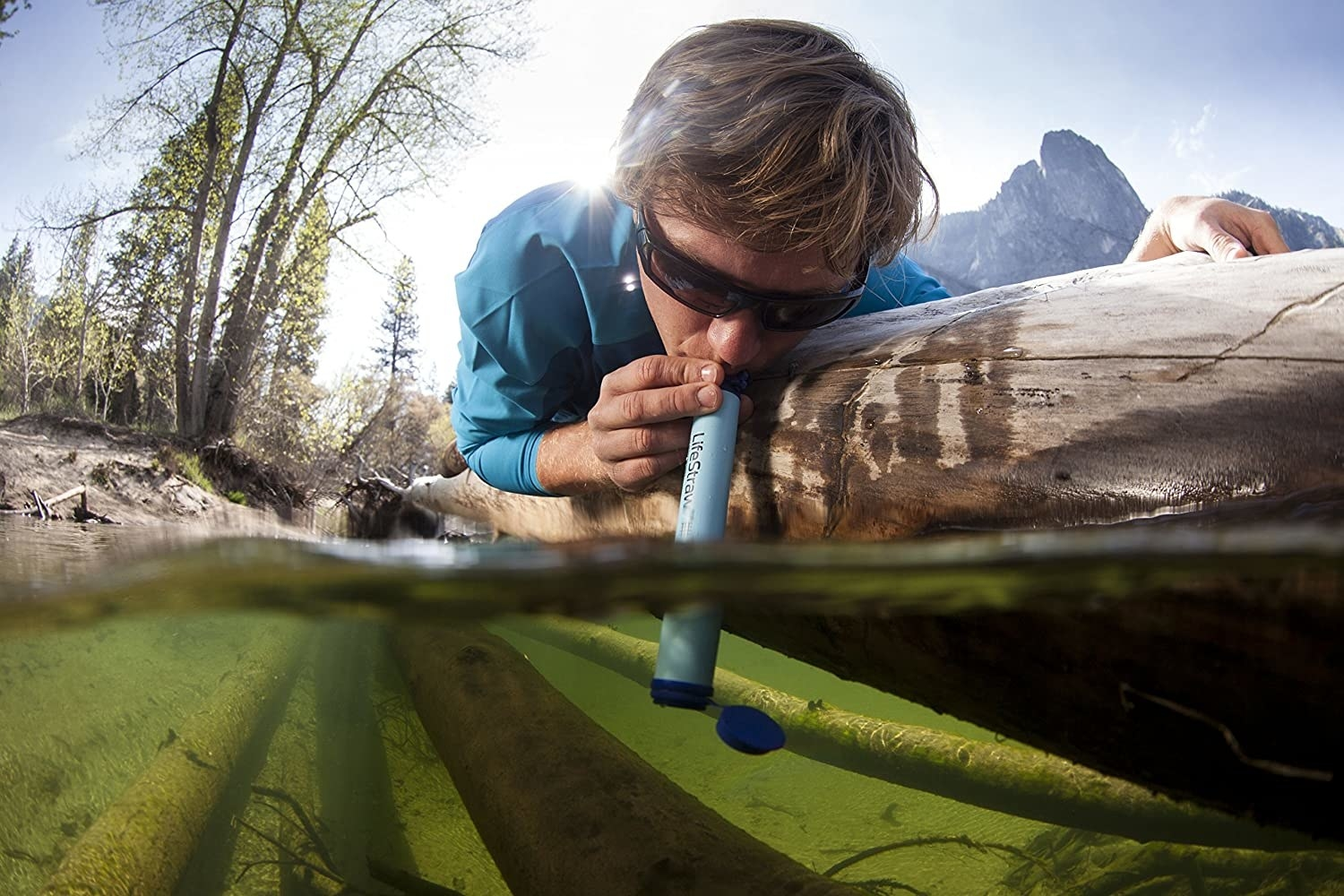 person drinking out of a lake with lifestraw
