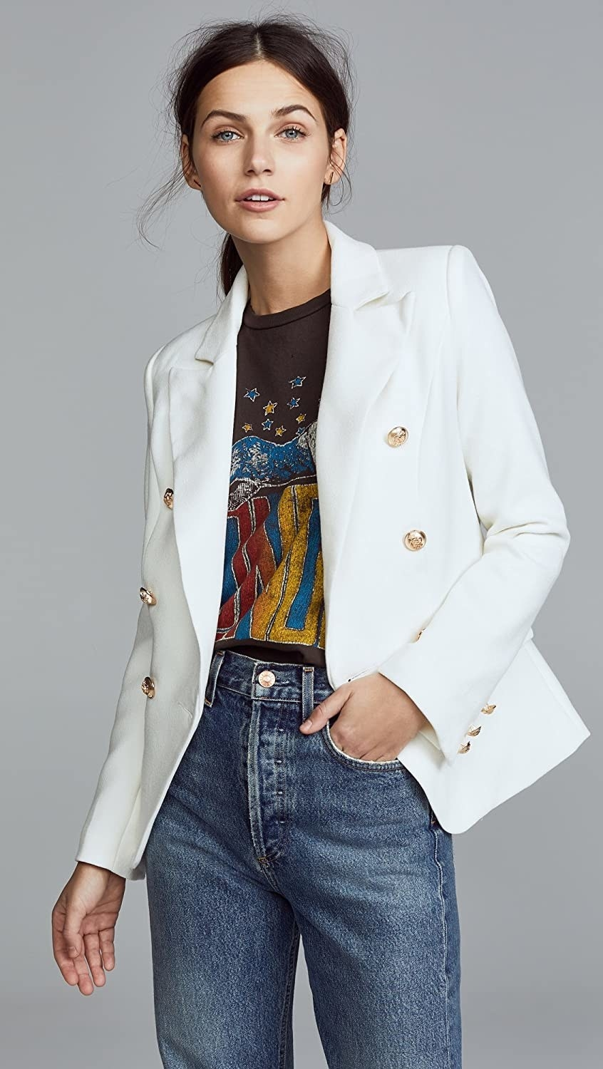 Person wearing white blazer with gold buttons with jeans and a graphic tee