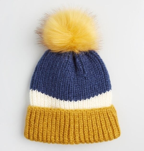 The gold, white, and blue striped beanie with a bright yellow pom pom