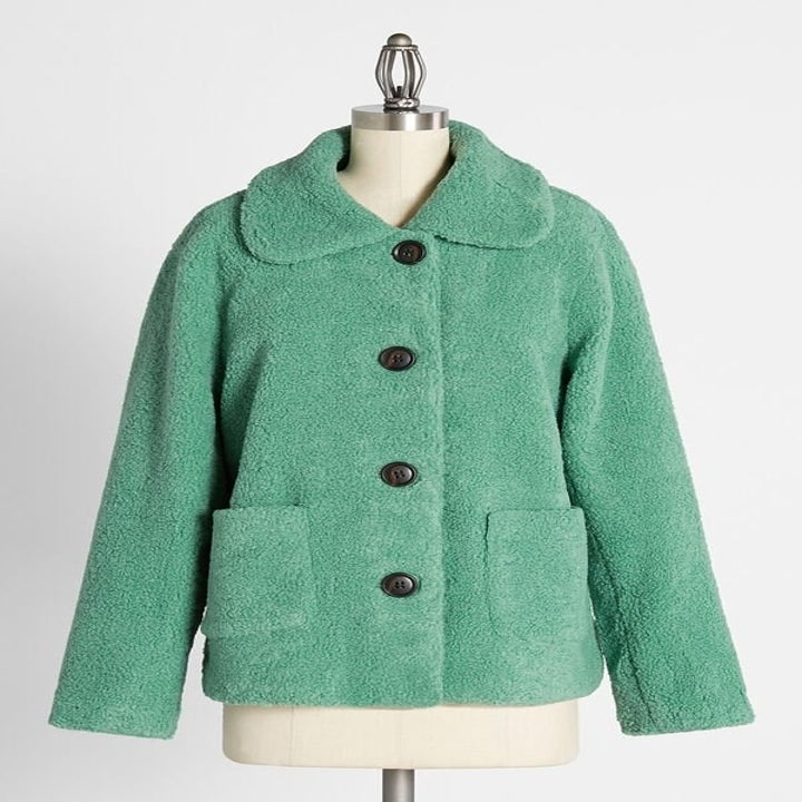 mint green plush jacket with round buttons, pockets, and a collar