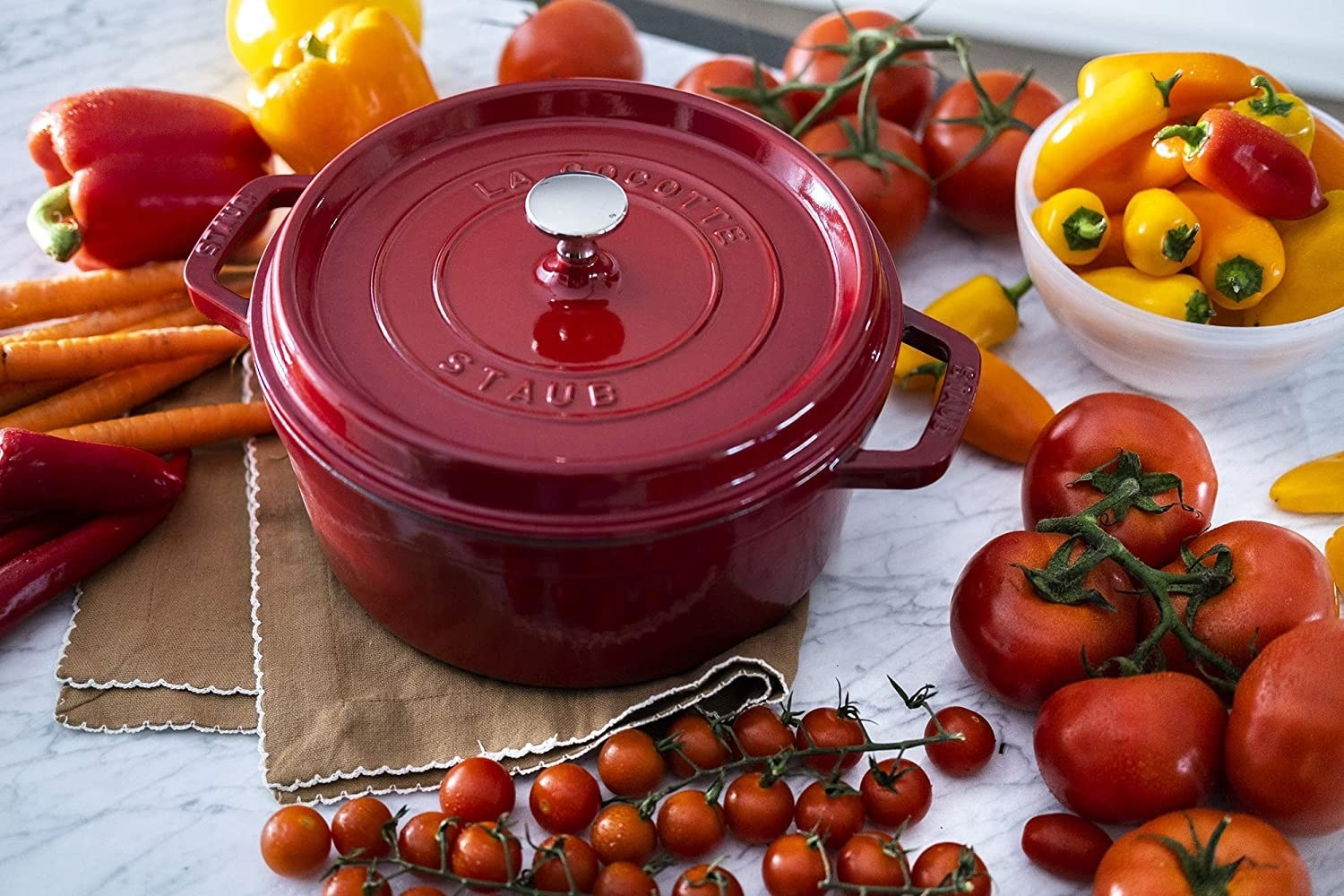 The red Dutch oven with cooked vegetables inside