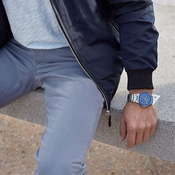 a model wearing a silve watch with a blue face