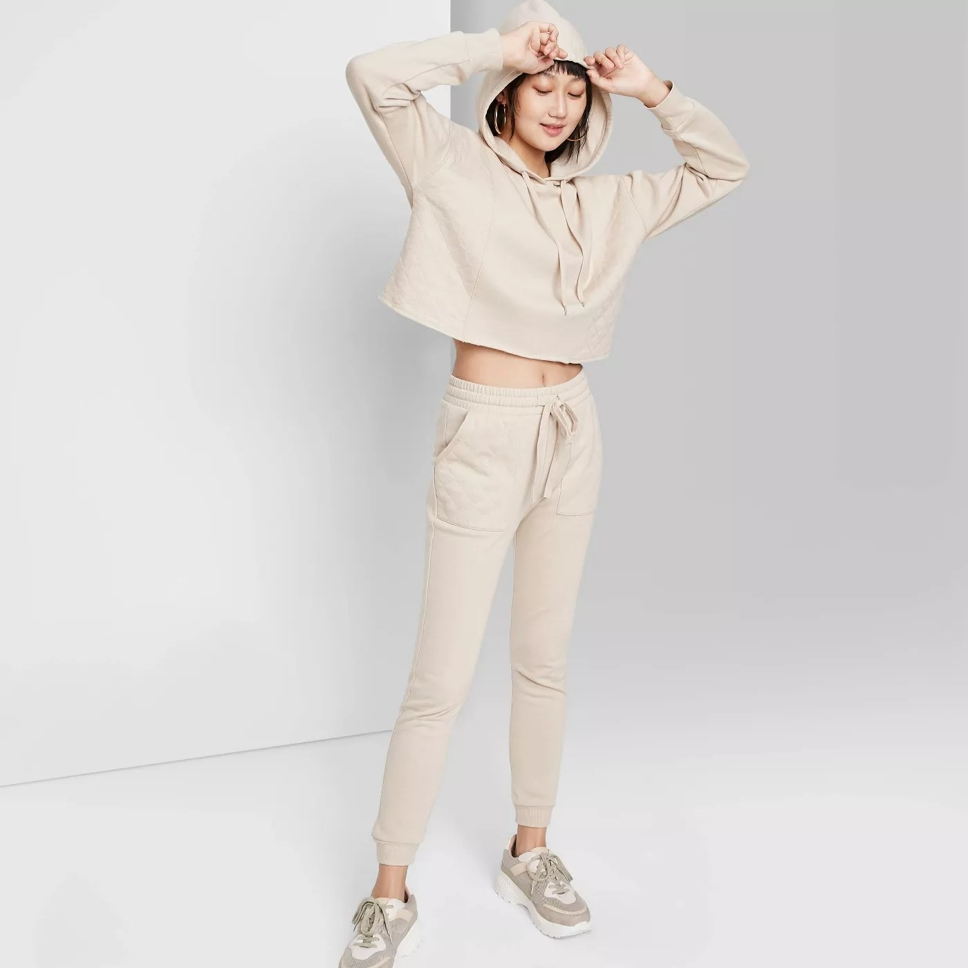 A model wearing the beige, high-waisted joggers with a matching hoodie