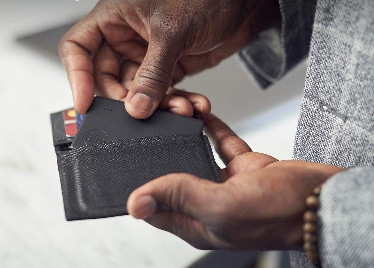 man putting tile in his wallet