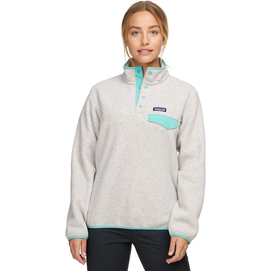 Model wearing the light gray mockneck pullover with teal lining and pocket flap