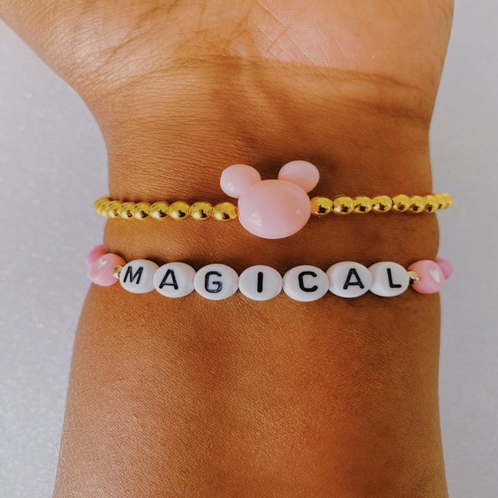 """model's arm wearing a bracelet that says """"Magical"""" with white and pink pearlized beads and another gold beaded bracelet with pink Minnie Mouse ears at the center"""