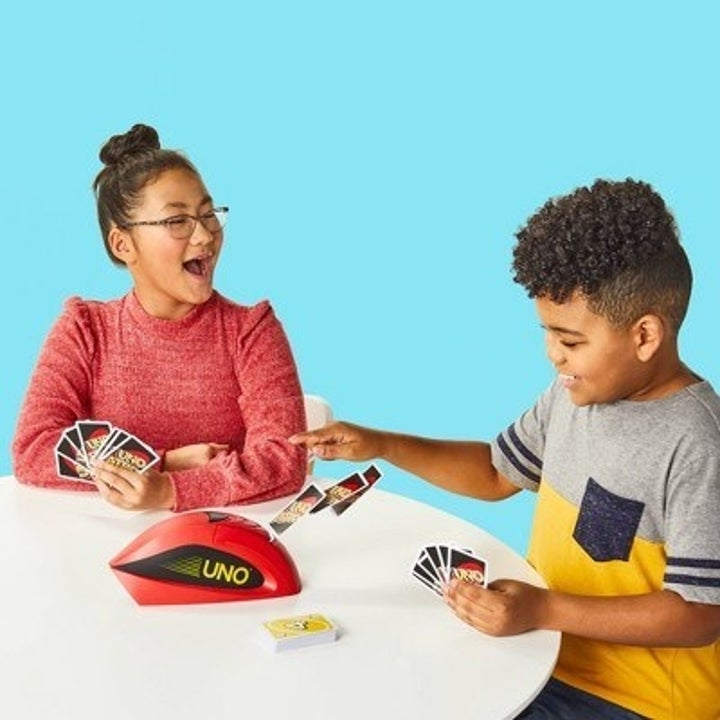 Two children playing the Uno Attack Game