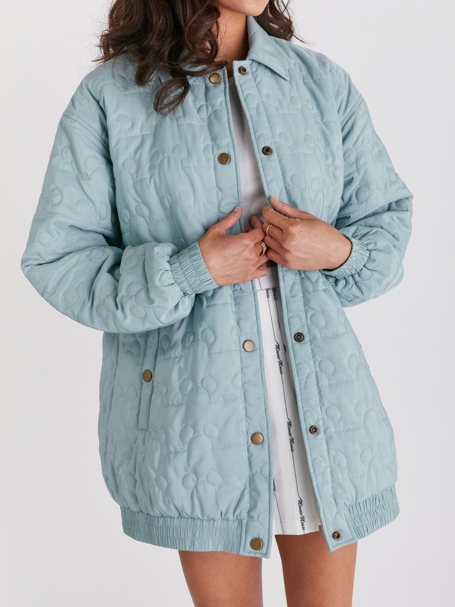 a model in a light blue quilted jacket