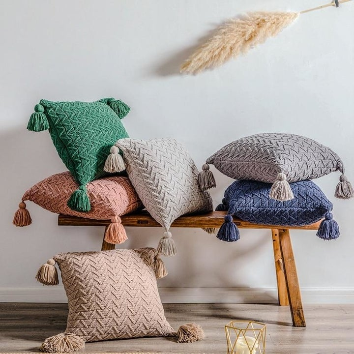 Pillows with covers that have knit texture and four tassels on each corner. There are five pillows on a bench and one of the floor.