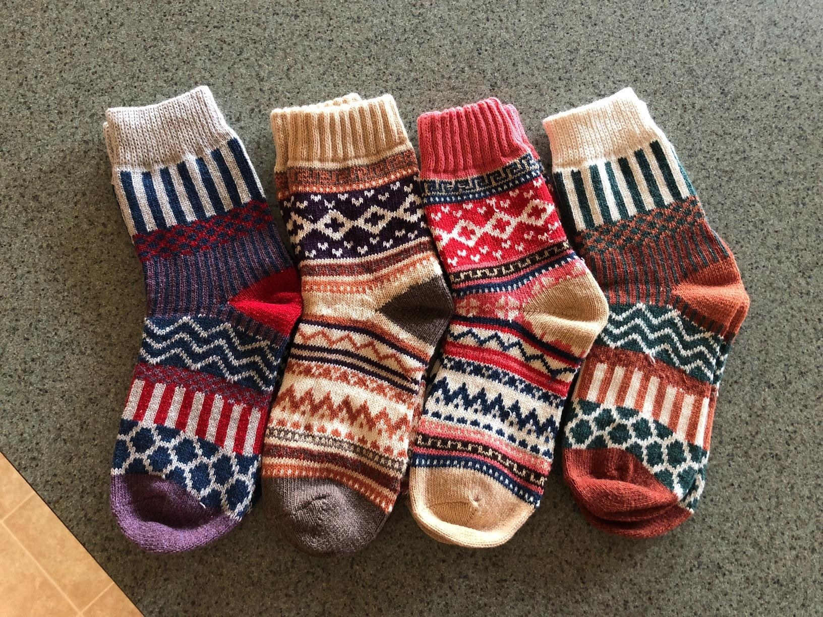 Reviewer photo of four socks in different colorful patterns