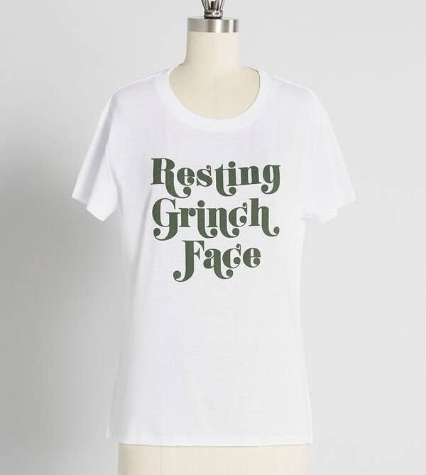 """A white T-shirt that says """"resting grinch face"""" in green text in the center"""