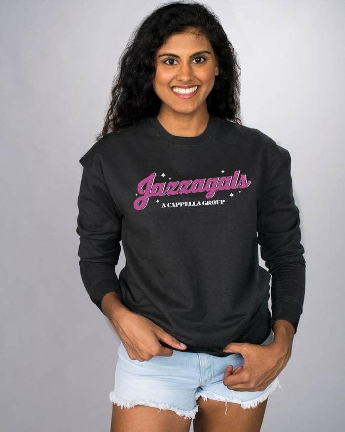 a model wearing a black sweatshirt with jazzagirls on it in pink