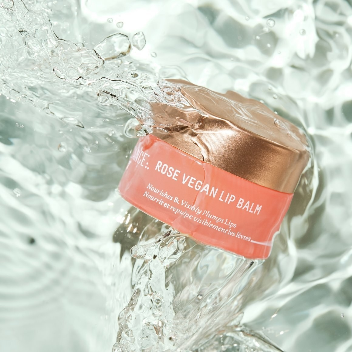 Pink and gold container of Biossance Rose Vegan Lip Balm in a water puddle