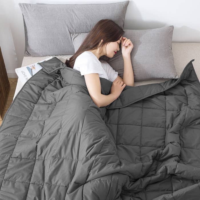 a woman sleeping on her bed underneath the weighted blanket in gray