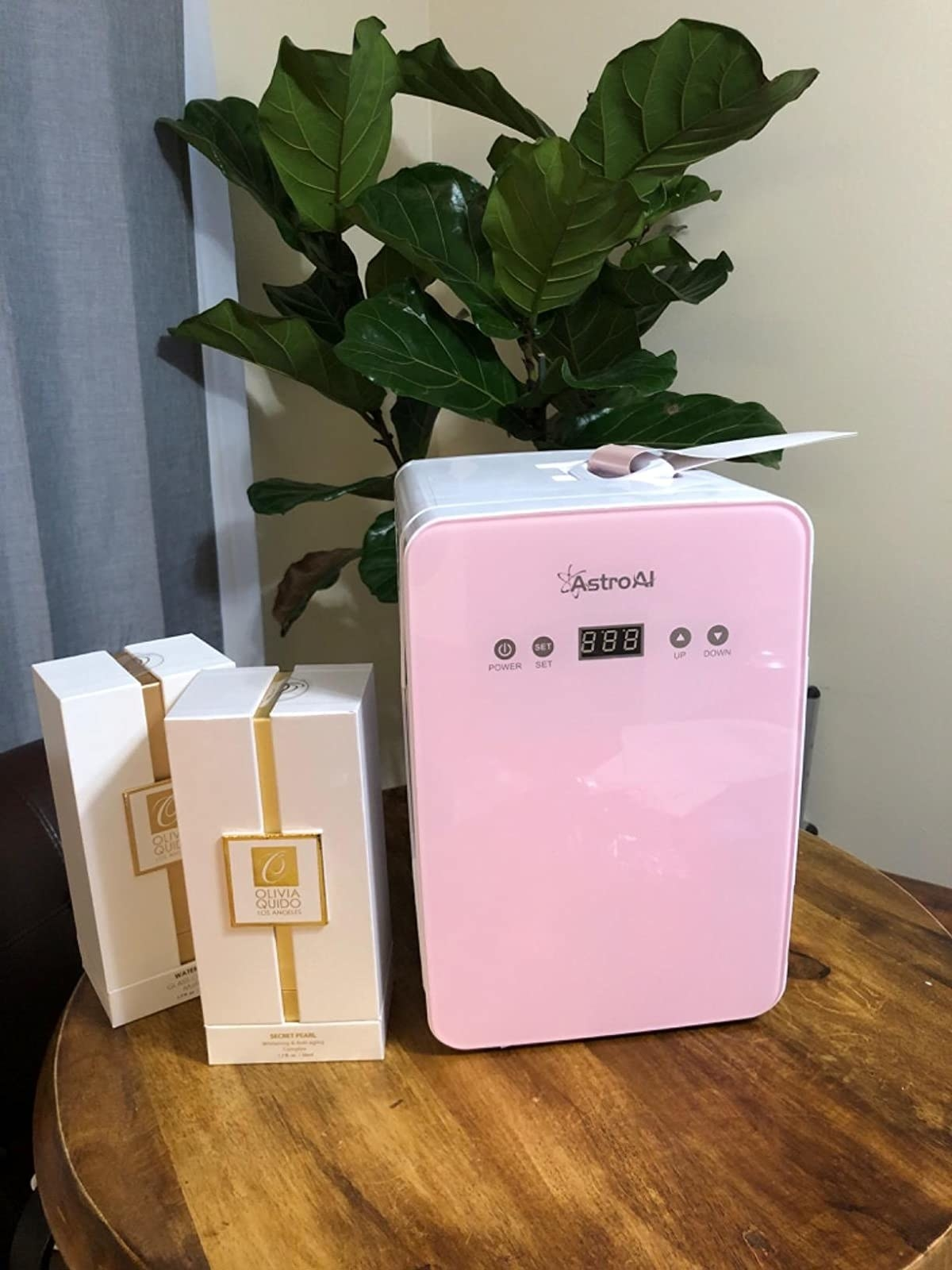 Reviewer pic of the small fridge with a pink door and controls on the top with beauty products next to it