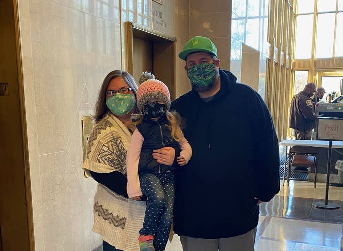 A family wearing masks stands near a security desk at the courthouse