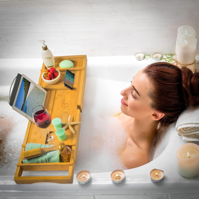 Model is in a bathtub watching a movie on her tablet on a bathtub caddy