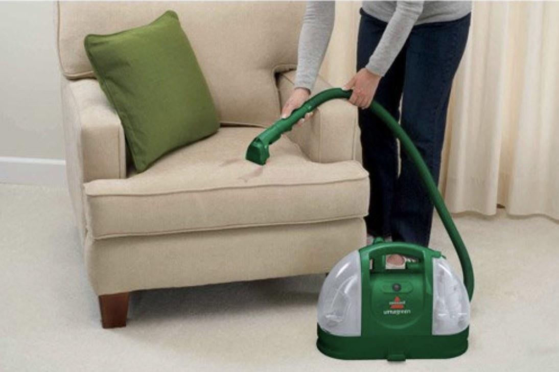 """模型是使用椅子上的绿色便携式污渍清洁剂""""class="""