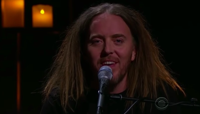Time Minchin smiles while singing into a microphone