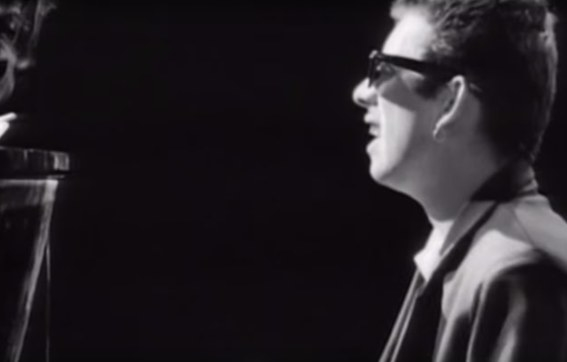 "Black and White still from the ""Fairytale of New York"" music video; Shane MacGowan  sings at at a piano, wearing sunglasses and a suit"