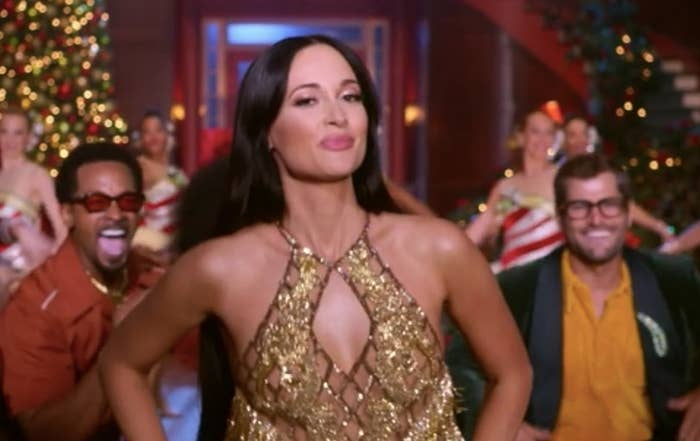 Kacey Musgraves dances in front of a cheering crowd in a room decorated for Christmas