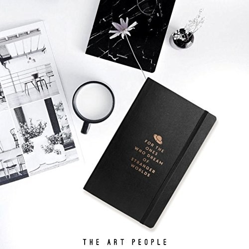 """A black journal which has the following phrase written in gold on its cover, """"For the ones who dream of stranger worlds"""". It's pictured with a mug, poster and plant."""