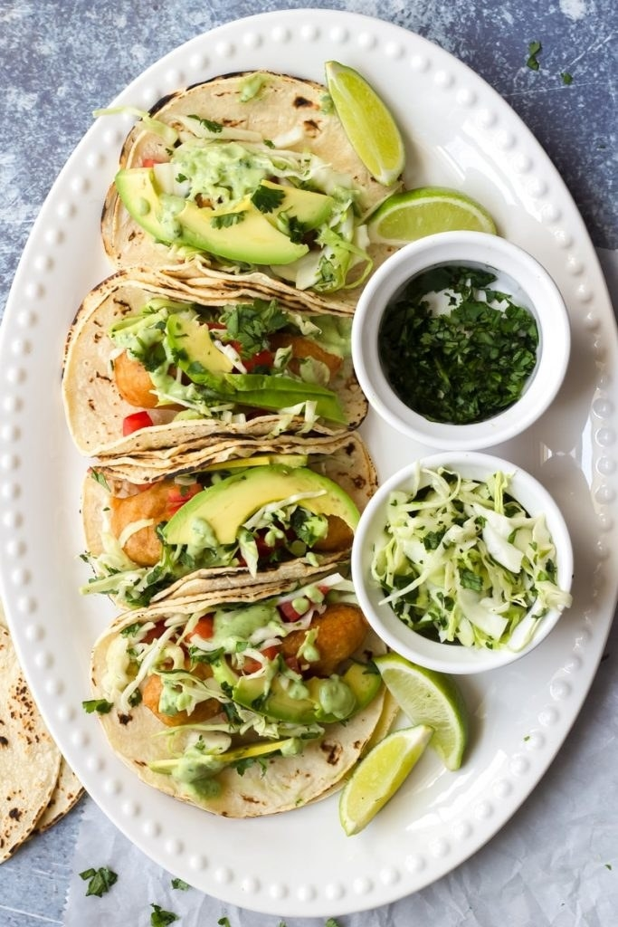 Three tacos filled with crispy fish and topped with avocado, slaw, and cilantro.