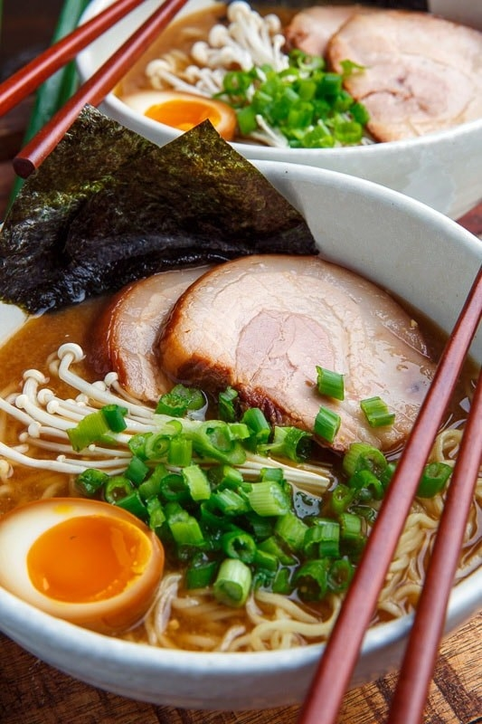 A bowl of ramen with pork belly, soft boiled eggs, enoki mushrooms, and scallions.