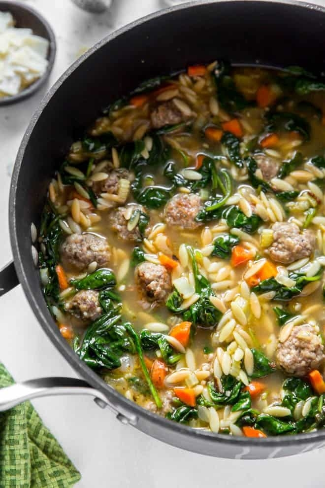 A pot of soup with orzo, mini meatballs, spinach, and carrots.