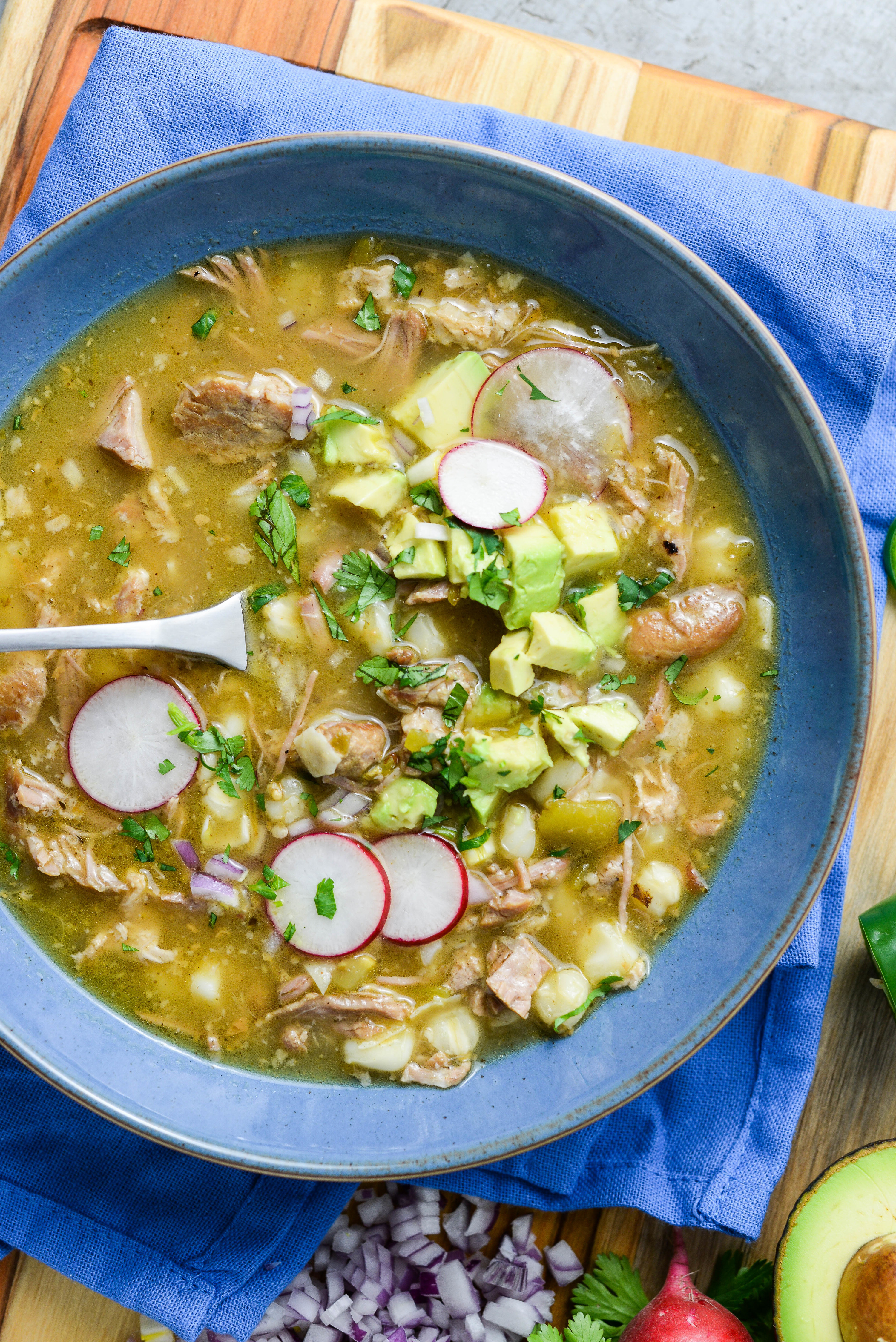 A bowl of green pozole with pork, hominy, radishes, chopped red onion, and avocado.