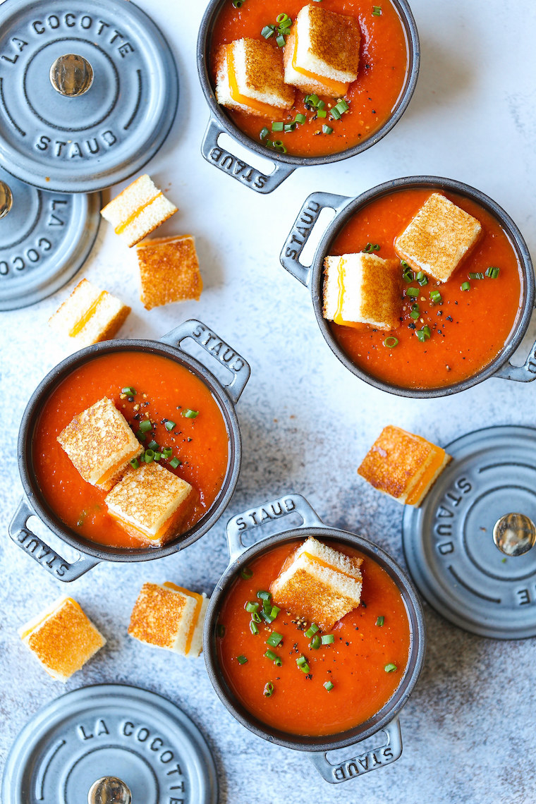 Four small cocottes filled with tomato soup topped with grilled cheese croutons.