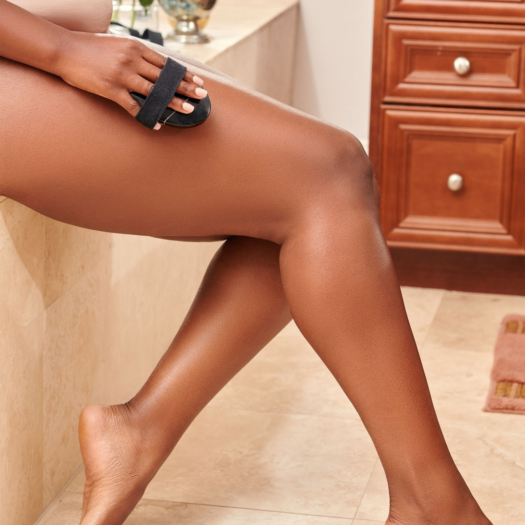 Model uses Gilded Body Marble Body Brush to exfoliate legs