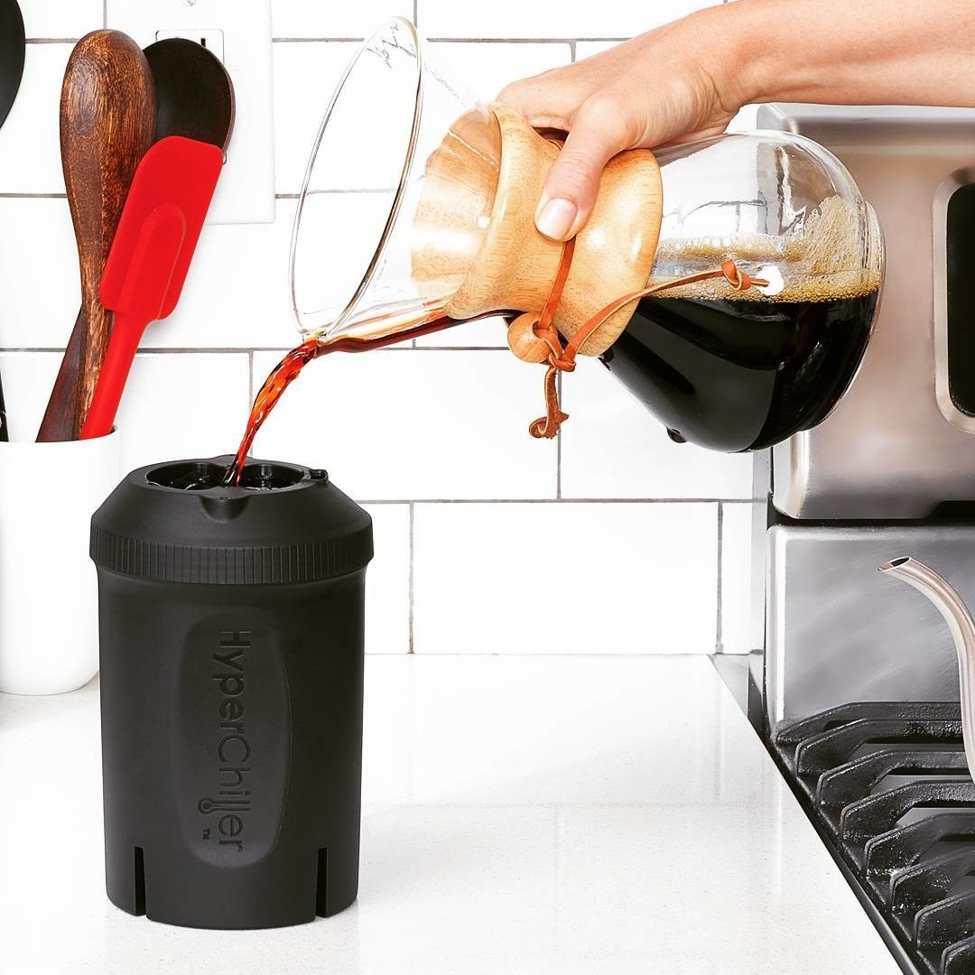 A person pouring coffee from a carafe into the drink cooler