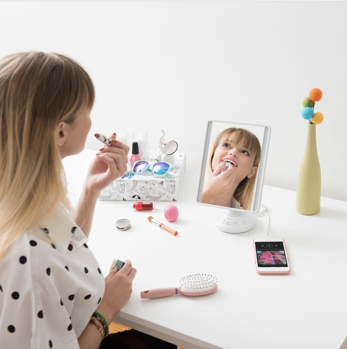 Person is applying makeup while looking into an iHome mirror