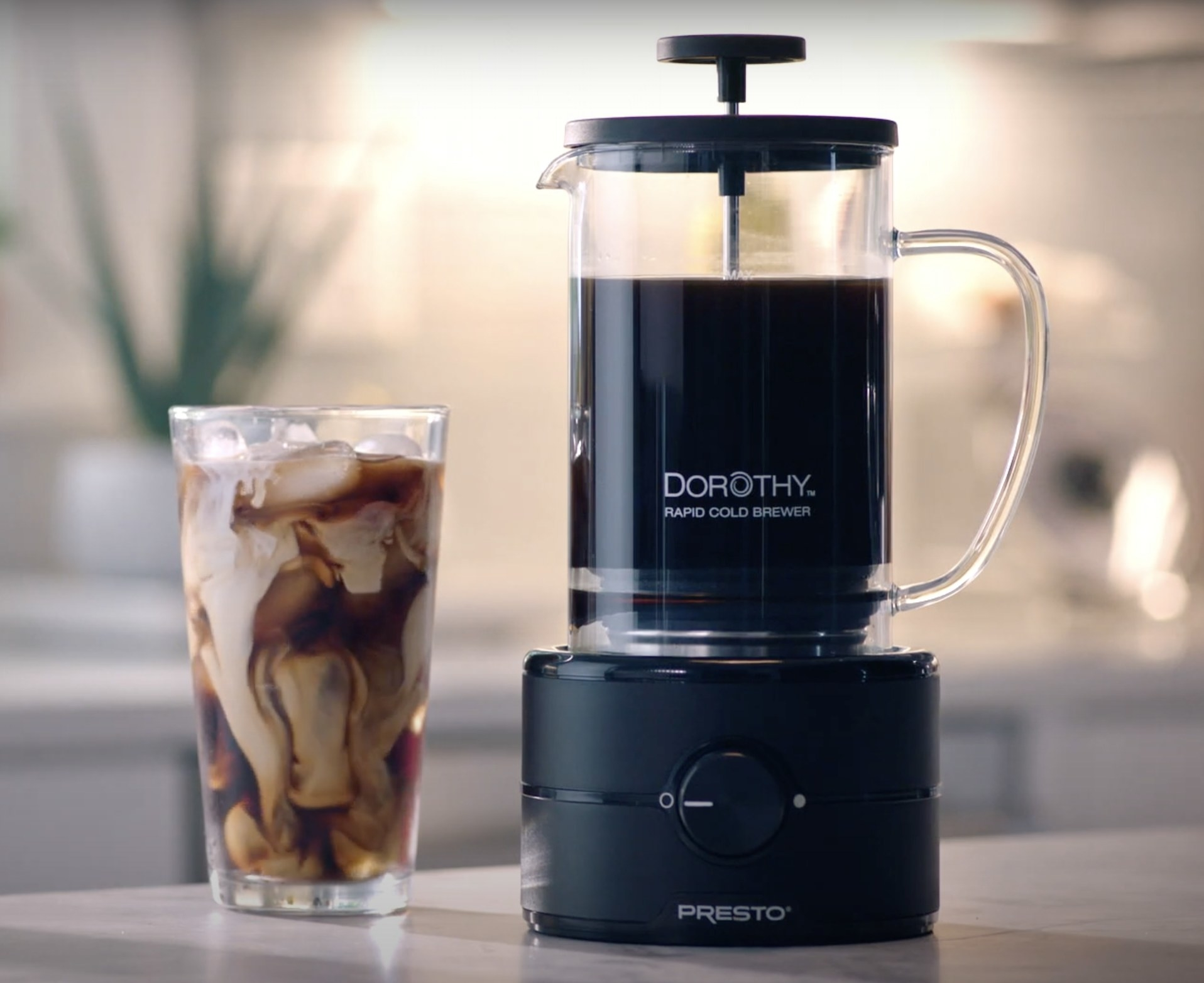 The cold brew maker next to a glass of iced coffee