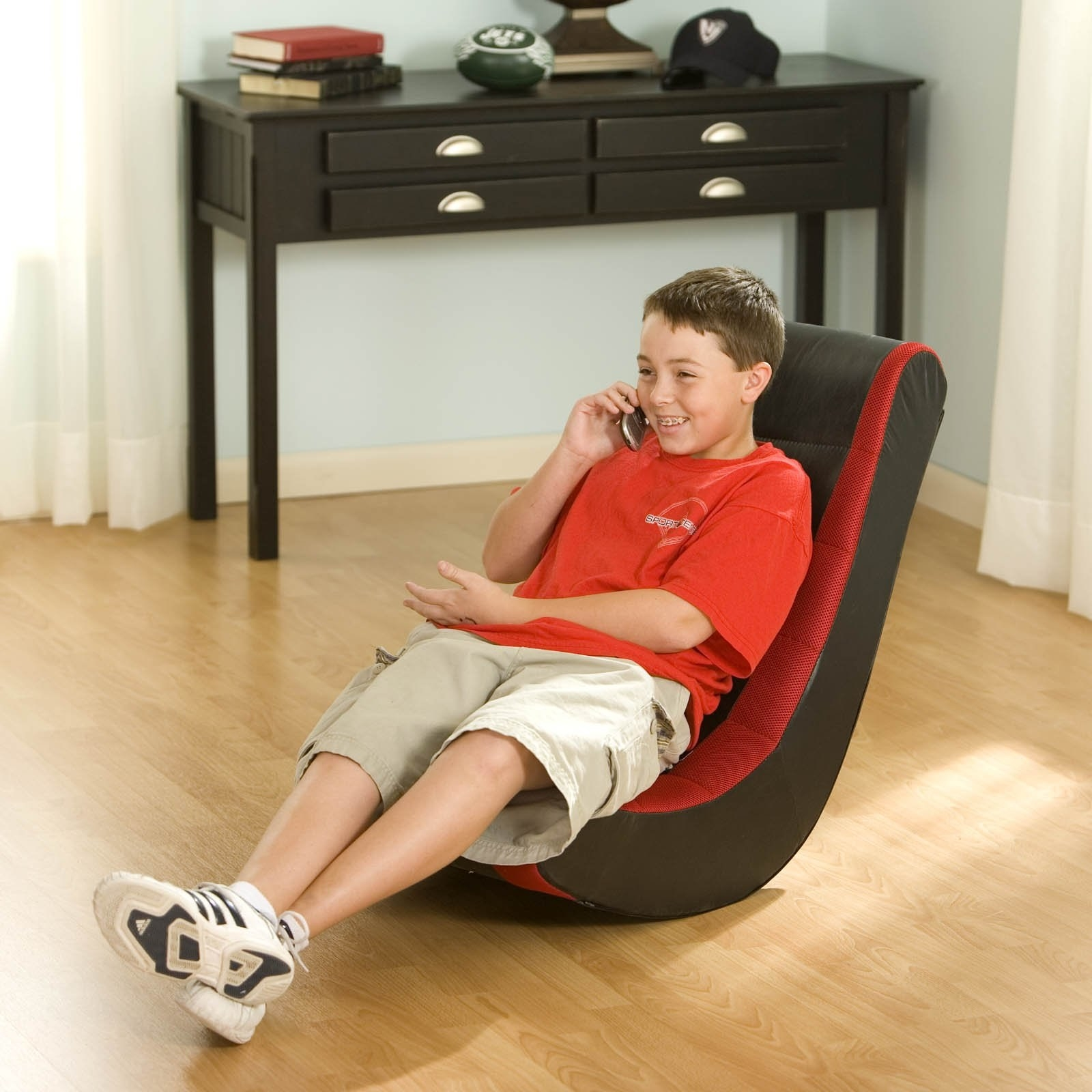 Model is sitting on the red and black gaming chair while talking on their phone
