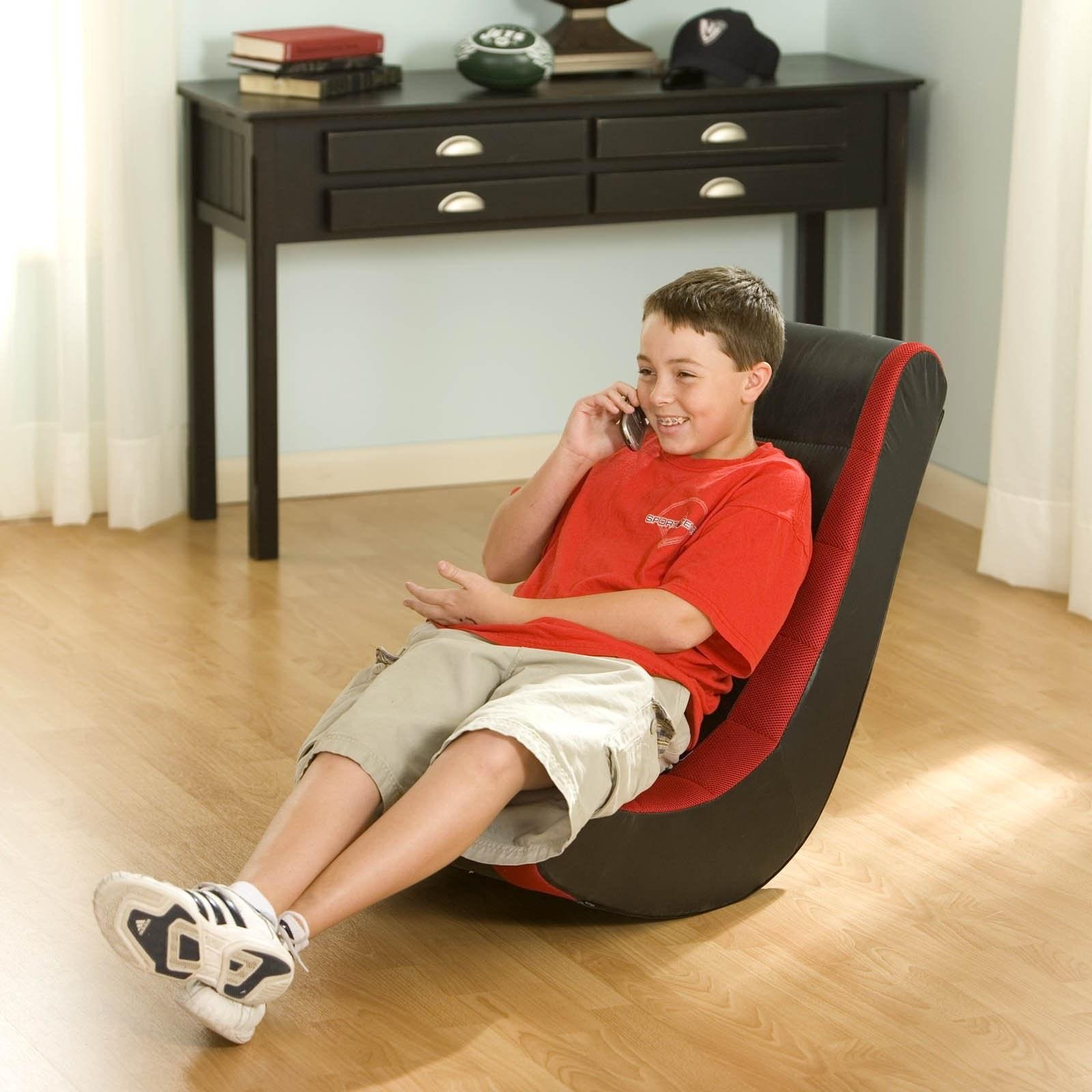 """模型坐在红色和黑色的游戏椅子上,而他们的电话交谈""""class="""