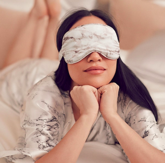 A person wears the silk eye mask while lounging in bed