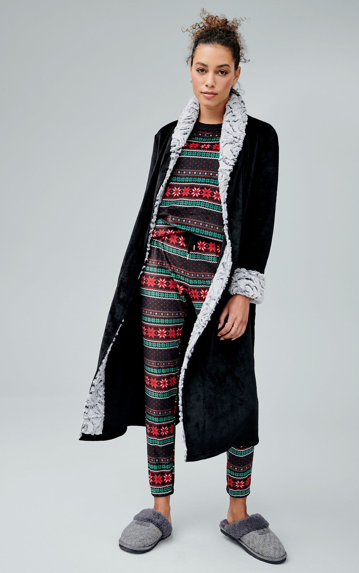 Model is wearing patterned Christmas pajamas under a black fuzzy robe