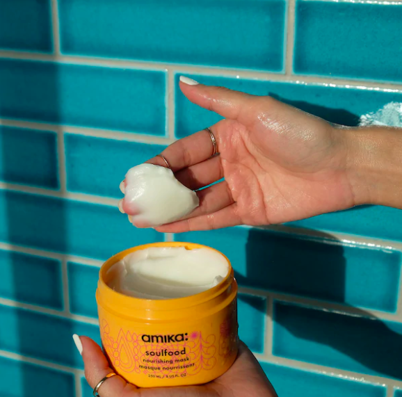 A person scoops some of the hair mask from the tub