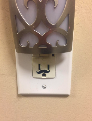 Reviewer's outlet with deodorizer plugged on top and mustache placed on bottom, making the outlet look like a face with a large hat on