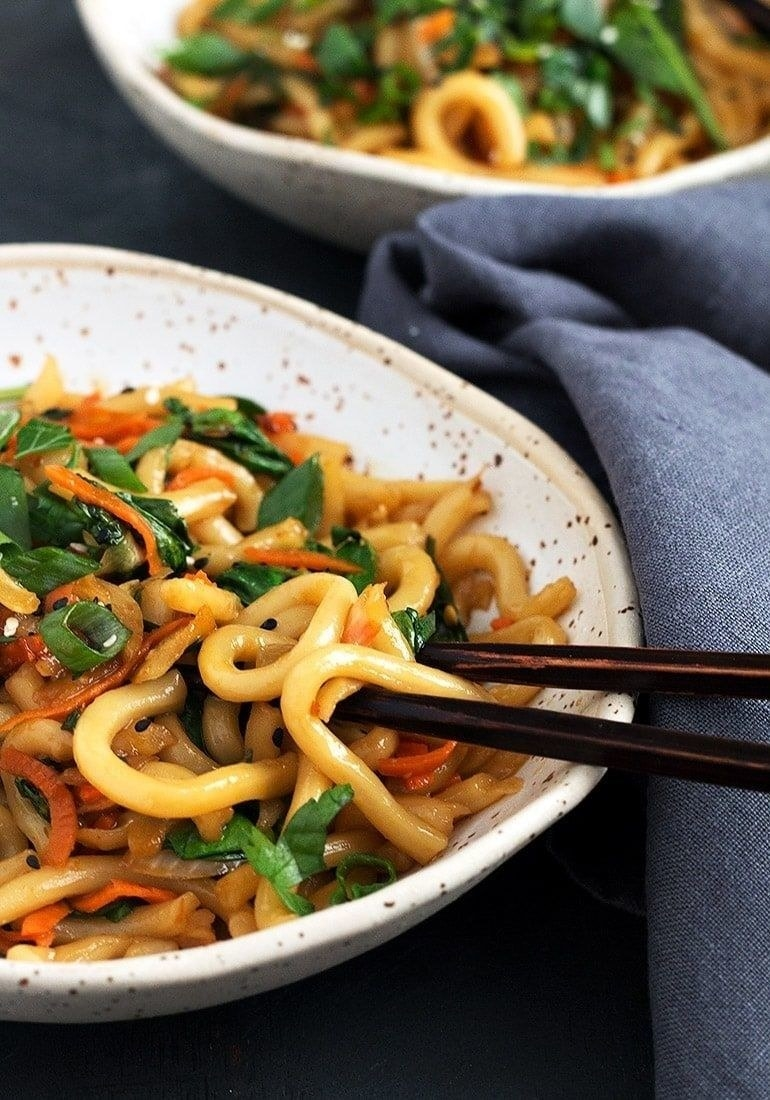 A bowl of udon noodle stir fry with carrots, scallions, and sesame seeds.