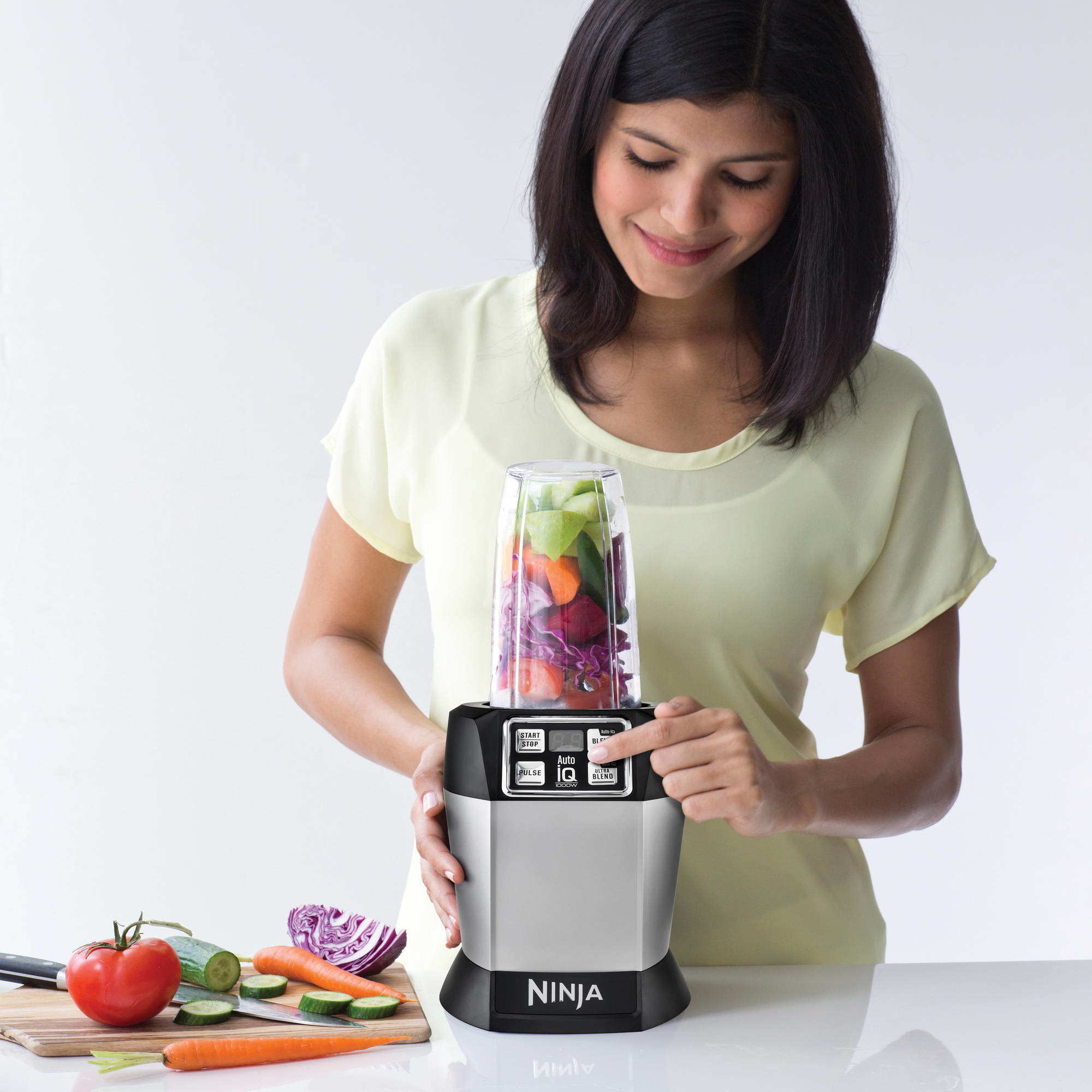 Model is pressing a button on a Ninja blender with veggies inside