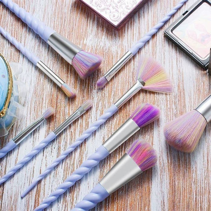 The brushes with purple unicorn-horn-looking twists for handles, silver metal connectors, and pastel yellow, pink, purple, and blue bristles