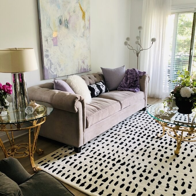a white rug with black polka dots on a living room floor under a couch