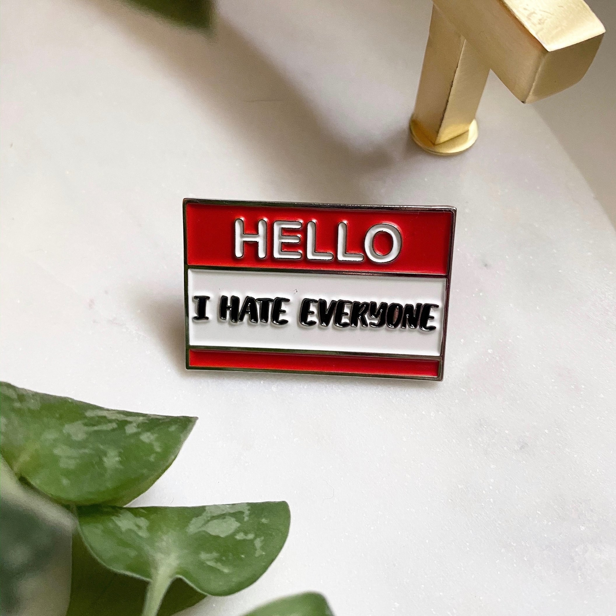 a red pin that looks like a name tag that says hello i hate everyone