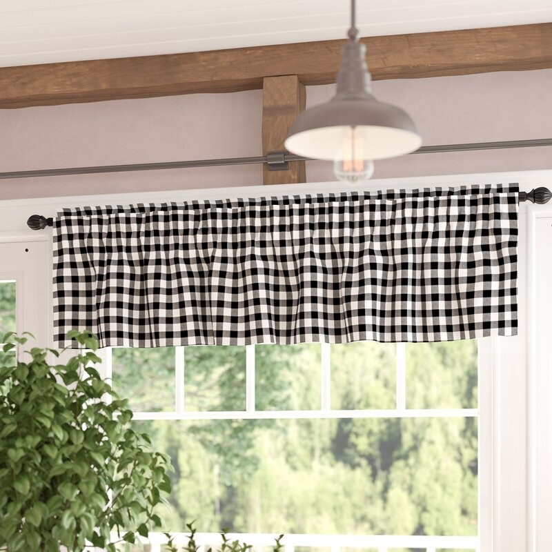 a black and white gingham valance in front of a window in a room